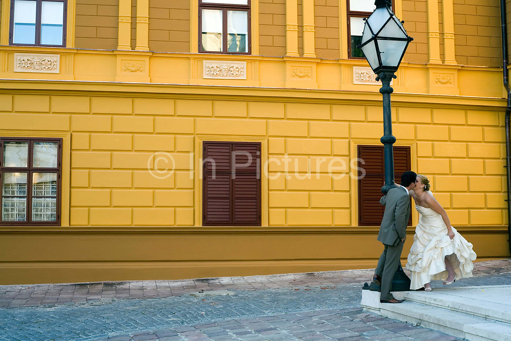 A newlywed couple pose for a photographer by the Bishop's Palace and Saint Peter's Church Pecs, Hungary.Pecs has been chosen as the 2010 European City of Culture. The city is on the southern slopes of the Mecsek Hills and has a sub-Mediterranean climate. Settled by Romans as Sopianae, it was a significant Christian settlement. Later conquered by the Ottomans, it has important Turkish architecture.