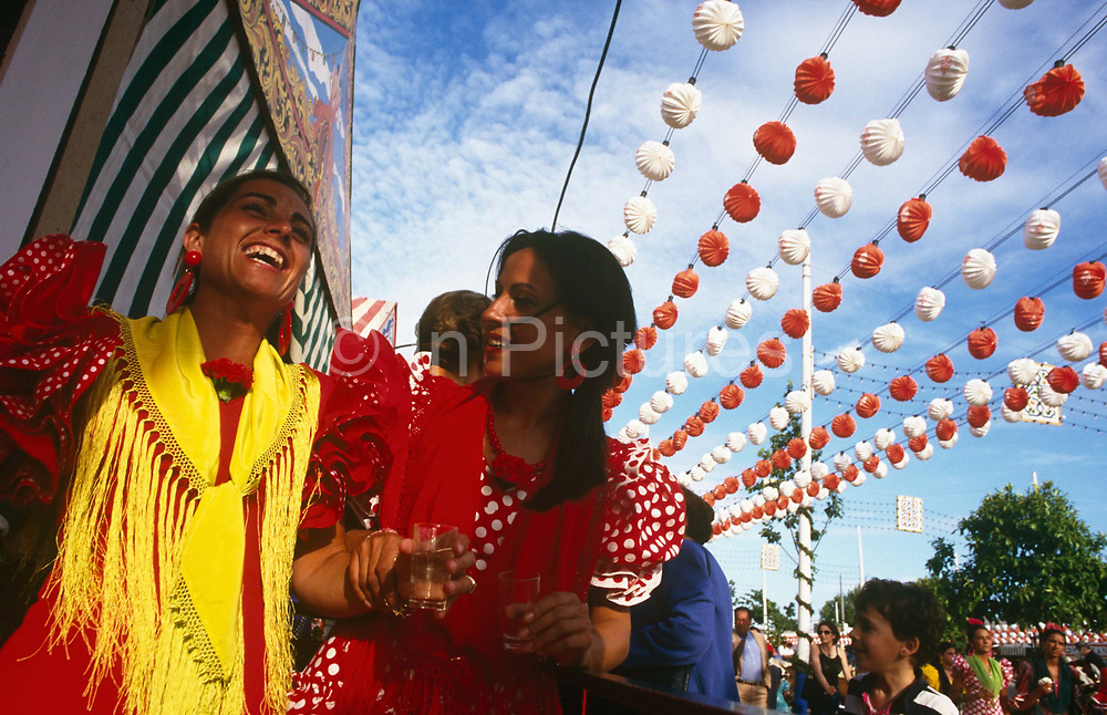 Two ladies are seen from a very low angle as they parade down an avenue during the Spring Feria in Seville, Spain. Beneath dozens of colourful decorations which hang from cables above their heads, they walk holding drinks laughing gaily. They are both dressed in traditional red and white flamenco dresses with red and yellow scarves around their necks. It is a lively event that Seville holds annually in the vast fairground area on the far bank of the Guadalquivir River. Rows of temporary marquee tents, or casetas, host families, corporations and friends into the late hours during the April Fair which begins begins two weeks after the Semana Santa, or Easter Holy Week in the Andalusian capital.
