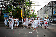 Locals wearing white clothes wait for warriors during a street procession. Every year during the ninth lunar month of the Chinese calendar, the Phuket Vegetarian Festival kicks off. The religious festival in Phuket, Thailand, lasts for 10 days, during which sacred rituals take place in the many Chinese shrines and temples. Walking on fire and climbing ladders with bladed rungs barefoot are two of several rituals believed to bring good fortune. The main purpose of the festival, however, is spiritual cleansing and merit-making. Participants of the festival adhere to a strict vegetarian diet for at least three days. This is one of the 10 main rules meant to ensure good hygiene and inner peace. Sex, alcohol, and meat are strictly forbidden. As cleanliness is considered to be of paramount importance, menstruating and pregnant women are not supposed to attend any of the rituals. The festival rules also call for impeccable mental and physical behavior as well as white clothing.
