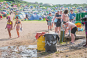 The reservoir supplying the sit is under pressure due to the heat and the lack of bottled water, with showers cloed people were washing at drinking stand pipes - The 2019 Glastonbury Festival, Worthy Farm. Glastonbury.