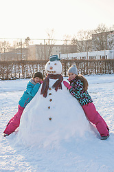Two girls leaning on snowman on snow field