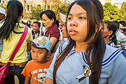 """30 JANUARY 2013 - PHNOM PENH, CAMBODIA:    A woman wearing a pin honoring King Sihanouk stops in front of the National Museum in Phnom Penh to look at the cremation site for late Cambodian King Norodom Sihanouk. Sihanouk (31 October 1922- 15 October 2012) was the King of Cambodia from 1941 to 1955 and again from 1993 to 2004. He was the effective ruler of Cambodia from 1953 to 1970. After his second abdication in 2004, he was given the honorific of """"The King-Father of Cambodia."""" Sihanouk held so many positions since 1941 that the Guinness Book of World Records identifies him as the politician who has served the world's greatest variety of political offices. These included two terms as king, two as sovereign prince, one as president, two as prime minister, as well as numerous positions as leader of various governments-in-exile. He served as puppet head of state for the Khmer Rouge government in 1975-1976. Most of these positions were only honorific, including the last position as constitutional king of Cambodia. Sihanouk's actual period of effective rule over Cambodia was from 9 November 1953, when Cambodia gained its independence from France, until 18 March 1970, when General Lon Nol and the National Assembly deposed him. Upon his final abdication, the Cambodian throne council appointed Norodom Sihamoni, one of Sihanouk's sons, as the new king. Sihanouk died in Beijing, China, where he was receiving medical care, on Oct. 15, 2012. His cremation is scheduled to take place on Feb. 4, 2013. Over a million people are expected to attend the service.        PHOTO BY JACK KURTZ"""