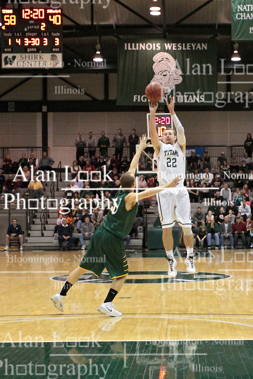 08 March 2014:  A long three by Jordan Nelson is barely contested by Andy Fox during an NCAA mens division 3 2nd Round Playoff basketball game between the St Norbert Green Knights and the Illinois Wesleyan Titans in Shirk Center, Bloomington IL