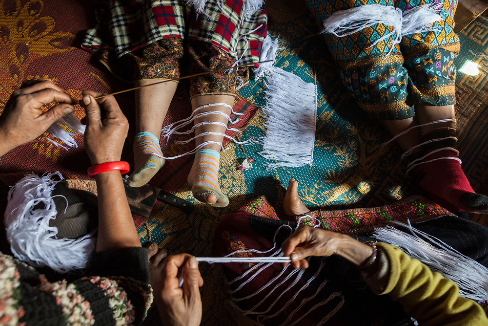 Women prepare white thread bracelets (representing good luck) at a celebration held at the home of a woman suffering from cancer in Ban Huay Phouk, Laos. According to her son, modern western medicine had failed to cure her so it was time to try a more traditional treatment.