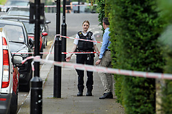 © Licensed to London News Pictures. 20/05/2019. London, UK. A police officer talks to a local resident at the scene in Little Venice, West London where a teenager has been repeatedly stabbed. Police were called to Warwick Avenue following a disturbance yesterday evening. The young man is currently in what has been described as life threatening condition. Photo credit: Ben Cawthra/LNP