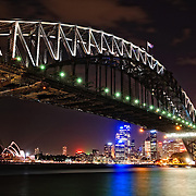 Night shot of Sydney Harbour Bridge and skyline of Sydney city looking back towards Dawes Point and taken from Milsons Point. The Sydney Opera House is at extreme left. Dawes Point is at right