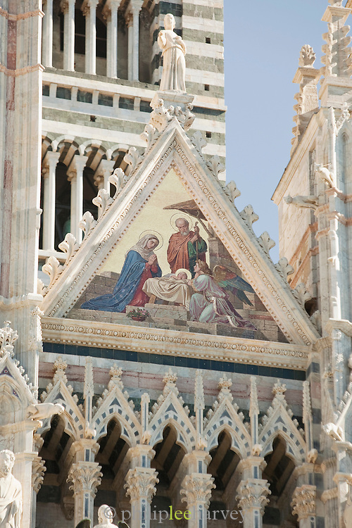 A fresco of a Catholic scene, showing the Virgin Mary and Jesus as a child, on the Duomo di Siena, Cathedral of Siena in Siena, Tuscany, Italy