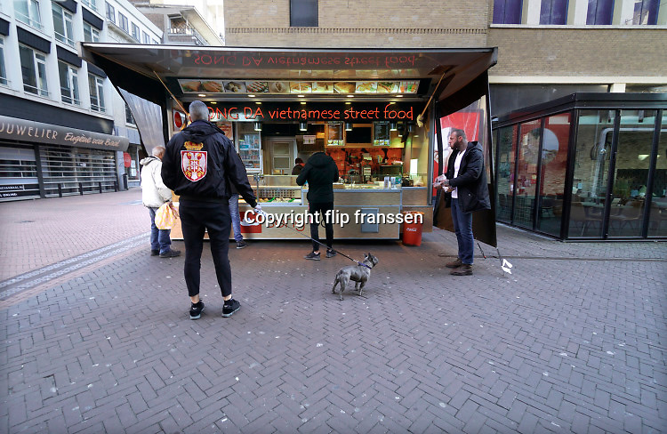 Nederland, Nijmegen, 25-3-2020 Lege binnenstad, uitgestorven stadscentrum . Winkels met maatregelen ivm het coronavirus. Een loempiaverkoper in de stad met klanten die 1,5 meter afstand van elkaar proberen te houden.Foto: Flip Franssen