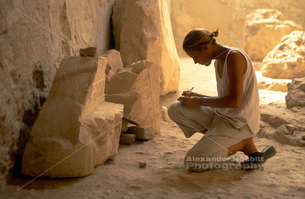 Archeologist makes a notes and drawing of relief carving in the tomb of Ramose in the Valley of the nobels, Luxor, Egypt