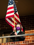 "08 APRIL 2020 - DES MOINES, IOWA: A woman wearing a face mask stands on her balcony and waves an American flag at Summit House, a condominium building for older adults. Residents are practicing ""social distancing"" and always wear masks when they go outside of their units. On Wednesday evenings they stand on their porches for a few minutes to wave at passing cars and socialize. On Wednesday, 08 April, Iowa reported 1,145 confirmed cases of the Novel Coronavirus (SARS-CoV-2) and COVID-19. There have been 27 deaths attributed to COVID-19 in Iowa. Most non-essential businesses are closed until 30 April. There have been outbreaks of Coronavirus in several Iowa senior citizen housing complexes.        PHOTO BY JACK KURTZ"