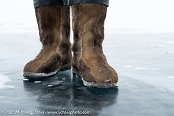 Russian custom bike builder Yaroslav Tatarinov stayed warm on the meter-thick ice in the middle of Lake Baikal in these Siberian made boots after the Baikal Mile Ice Speed Festival. Maksimiha, Siberia, Russia. Sunday, March 1, 2020. Photography ©2020 Michael Lichter.