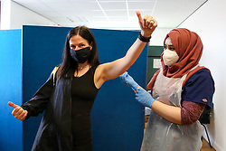 © Licensed to London News Pictures. 21/03/2021. London, UK. A woman gestures after receiving the first dose of Oxford AstraZeneca Covid-19 vaccine by a NHS staff at Masjid Ayesha, a mosque in Tottenham, north London. The mosque is working in partnership with Federated4Health and is encouraging local communities to be inoculated. The government announced that over 26 million people have now received a first dose of a vaccine and over 2 million have received their second dose of a vaccine. Prime Minister Boris Johnson received his first dose on Friday. <br /> <br /> ***Permission Granted***<br /> <br /> Photo credit: Dinendra Haria/LNP