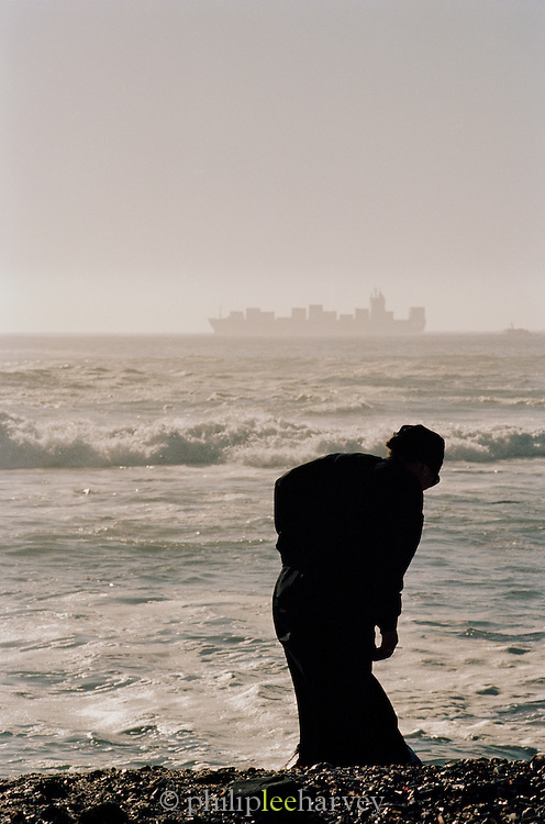 A woman scavaging on the coast, with a large container ship on the horizon, at Cape Town, South Africa