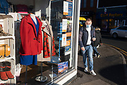 On the last day of the year, people pass a closed charity shop wearing masks along Kings Heath High Street, as many shops remain closed, with shutters down due to Tier Four coronavirus restrictions on 31st December 2020 in Birmingham, United Kingdom. Small businesses have struggled through the Covid-19 pandemic and many have closed down altogether, as the recession in the economy deepens as the crisis continues.