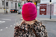 Woman with blonde hair wearing a Leopard print fur coat in and a bright shocking pink wool hat in London, United Kingdom.