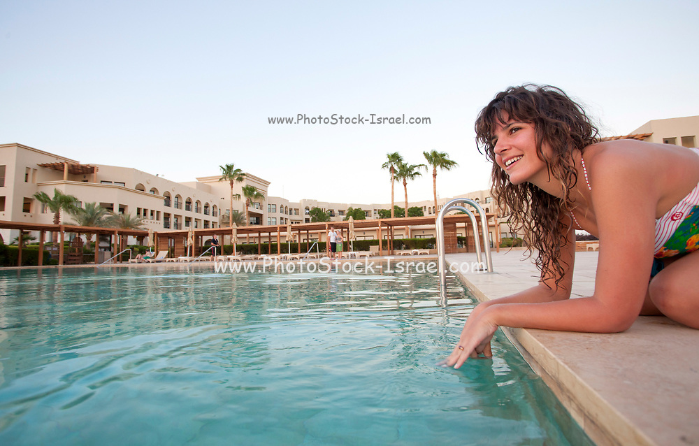 Jordan, Aqaba, Tala Bay Luxury Beach Resort young woman by the swimming pool - Model release available