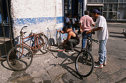 Workers pumping air into bicycle tyres and repairing bicycles at a repair shop or Ponchera in Havana; Cuba,