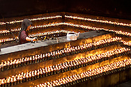 A Tibetan nun lights hundreds of prayer candles at The Jokang, Tibetan Buddhism's most holy temple.  Lhasa, Tibet.