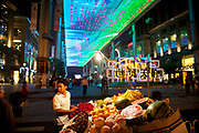 Fruit seller at The Place is a new shopping street located in Beijing CBD. The huge overhead LCD screen designed by Jeremy Railton from Hollywood, is 250m long 30m wide. The Beijing Central Business District, or CBD is the primary area of finance, media, and business services in Beijing, China. It occupies 4 km2 of the Chaoyang District on the east side of the city. As the city is becoming one of the most important international financial centers in China so the CBD grows in height as skyscrapers rise into the sky.