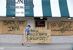 Local resident John Branigan, 65, one of the few islanders choosing to ride out Hurricane Irma and Hurricane Jose, passes by the closed and boarded-up Bernie's Oyster House on Saturday, September 9, 2017, on Tybee Island, Ga. Photo by Curtis Compton/Atlanta Journal-Constitution/TNS/ABACAPRESS.COM