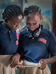 4 November 2019, Vriginia, Liberia: Two female students work on a tablet together during recess at Ricks Institute. The Liberia Baptist Convention runs Ricks Institute, a day and boarding school for currently 496 students from kindergarten up through 12th grade.