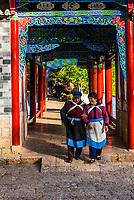 Naxi minority women walking in Black Dragon Pool Park, Lijiang, Yunnan Province, China.