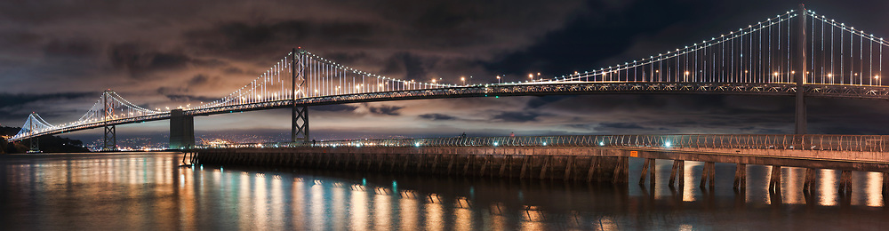 The lights of the San Francisco-Oakland Bay Bridge shimmer on the bay as pier 14 is seen in the foreground from along the embarcadero.