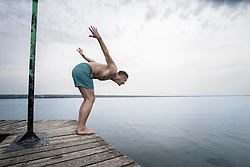 Mature man diving into water on pier, Bavaria, Germany