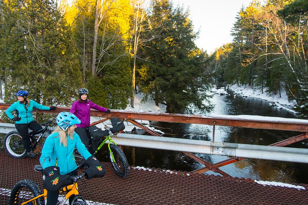 Taking a break on a bridge over the scenic Dead River while winter cycling fat biking snow biking in Marquette, Michigan.