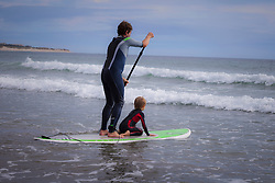 Father with his son paddleboarding in the sea, Viana do Castelo, Norte Region, Portugal