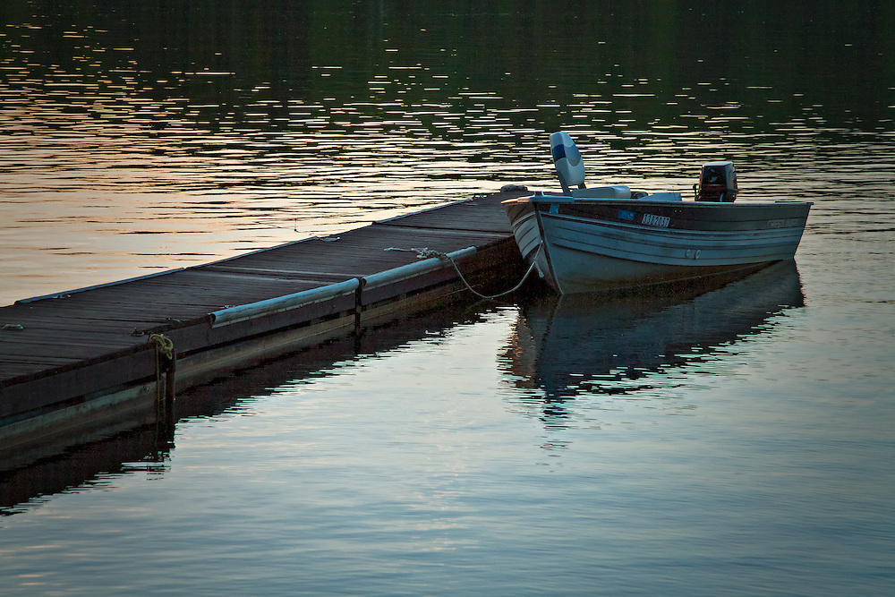 A boat waits to be ridden tomorrow as the sun sets.