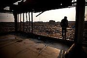 Ishinomaki  Quartier Minami Hamacho  commémoration   11 mars 2012.Il ne reste plus rien du quartier résidentiel Minami Hamacho.  En ce jour commémoratif, un grand nombre de bus venant des différentes régions du Japon sont venus pour pour constater limpassable et accompagner de leur présence la population dIshinomaki. Beaucoup sarrète dans ce qui était anciennement un convenient store (superette), aujourdhui, simple structure métallique.