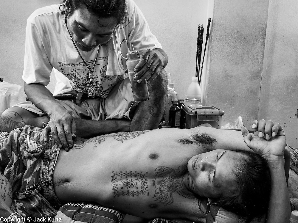 """14 MARCH 2014 - NAKHON CHAI SI, NAKHON PATHOM, THAILAND: A man grimaces as he gets a sak yant tattoo at Wat Bang Phra. Wat Bang Phra is the best known """"Sak Yant"""" tattoo temple in Thailand. It's located in Nakhon Pathom province, about 40 miles from Bangkok. The tattoos are given with hollow stainless steel needles and are thought to possess magical powers of protection. The tattoos, which are given by Buddhist monks, are popular with soldiers, policeman and gangsters, people who generally live in harm's way. The tattoo must be activated to remain powerful and the annual Wai Khru Ceremony (tattoo festival) at the temple draws thousands of devotees who come to the temple to activate or renew the tattoos. People go into trance like states and then assume the personality of their tattoo, so people with tiger tattoos assume the personality of a tiger, people with monkey tattoos take on the personality of a monkey and so on. In recent years the tattoo festival has become popular with tourists who make the trip to Nakorn Pathom province to see a side of """"exotic"""" Thailand.   PHOTO BY JACK KURTZ"""