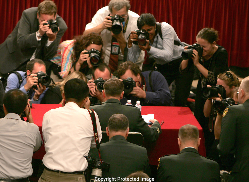 Photographers record  General David Petraeus getting his papers in order before his testimony at the Senate Foreign Relations Committee in Washington, D.C. on September 11, 2007.  Photograph: Dennis Brack