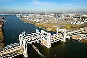 Nederland, Zuid-Holland, Rotterdam, 18-02-2015; bouw van de nieuwe Botlekbrug, binnenvaartschip passeert de nieuwe brug. De brug over de Oude Maas is een hefbrug, een van de twee brugdelen in geheven toestand. De heftorens van de oude brug gaan verscholen achter de nieuwe brug.<br /> Construction of the new Botlek bridge.<br /> The bridge over the Oude Maas is a vertical-lift bridge or lift bridge, one of the two bridge sections raised. <br /> luchtfoto (toeslag op standard tarieven);<br /> aerial photo (additional fee required);<br /> copyright foto/photo Siebe Swart