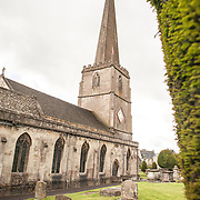 Cemetary and steeple at the Parish Church of St Mary in Painswick, Gloucestershire, in England's Cotswolds region. At right is part of the church's famous Yew trees.