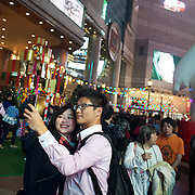 A young couple in Times Square takes a selfie on their mobile phone with Christmas decorations in the back ground. Times Square is a popular shopping area and Christmas is particularly busy. 7 million people live on 1,104km square, making it Hong Kong the most vertical city in the world.
