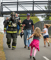 """In full gear weighing approximately 60 lbs. Laconia Firefighter Andy Francis walks the """"Take the Trail Fun Walk"""" alongside honorary member Alan Hopkins during the WOW Fest event held Saturday morning.   (Karen Bobotas/for the Laconia Daily Sun)"""