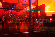 Red-tinted window landscape caused by the Serpentine Gallery's Pavilion. Young visitors gather to talk and drink within the main structure of the Serpentine's 40th Anniversary—the Serpentine Gallery Pavilion is designed by world-renowned French architect Jean Nouvel. The entire design is rendered in a vivid red that, in a play of opposites, contrasts with the green of its park setting. In London, the colour reflects the iconic British images of traditional telephone boxes, post boxes and London buses. The building consists of bold geometric forms, large retractable awnings and a sloped freestanding wall that stands 12m above the lawn. Striking glass, polycarbonate and fabric structures create a versatile system of interior and exterior spaces.