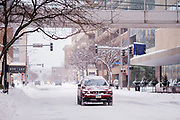 26 JANUARY 2021 - DES MOINES, IOWA: Traffic on a snow packed street in downtown Des Moines. Workers in Des Moines started cleaning up a record snowfall Tuesday morning. The National Weather Service reports that 10.3 inches of snow fell at Des Moines International Airport Monday, January 25, breaking the daily record of 10 inches for January 25 set in 1895. Many downtown businesses closed for the day because of the snow, since roads throughout central Iowa were snowpacked and hard to drive.        PHOTO BY JACK KURTZ