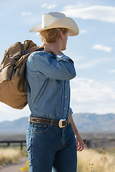 cowboy with a bag looking towards a mountain range