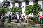People appear to drink across various onsite and beside the river makeshift pubs in Hackney Wick, East London on Saturday, July 4, 2020, as England welcome reopening day by welcoming back customers for the first time after the COVID-19 lockdown. England is embarking on perhaps its biggest lockdown easing yet as pubs and restaurants have the right to reopen for the first time in more than three months. (VXP Photo/ Marcin Nowak)