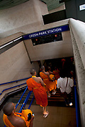 Young Tibetan Buddhist monks walk through Green Park and down into the underground station. The special dress of ordained people, the robes, comes from the idea of wearing cheap clothes just to protect the body from weather and climate. Monks often make their own robes from cloth that is donated to them. They shall not be made from one piece of cloth, but mended together from several pieces. Since dark red was the cheapest colour in Kashmir, the Tibetan tradition has red robes. In the south, yellow played the same role, though the color of saffron also had cultural associations in India; in East Asia, robe color varies from yellow to brown (Thailand, Theravada), red to purple (Burma, Theravada) and grey or black (e.g., Vietnam, Vajrayana (Zen).