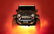 Jeep JK with Flog Industries custom bumpers. Image of a jeep surrounded by red fog. Glowing light coming from underneath. It's an advertising photograph for Flog Industries bumpers