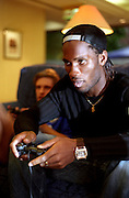 Chelsea footballer Didier Drogba playing video games in a Heathrow hotel in 2005, published in Max magazine, France, September 2005