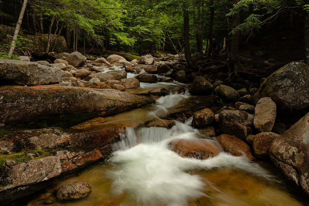 Mountain water rushing down a boulder lined brook in the mountains of New Hampshire.