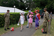 Chic women (and a man) walk past serving Coldstream Guards soldiers collecting cash for charity during the annual Royal Ascot horseracing festival in Berkshire, England. Royal Ascot is one of Europe's most famous race meetings, and dates back to 1711. Queen Elizabeth and various members of the British Royal Family attend. Held every June, it's one of the main dates on the English sporting calendar and summer social season. Over 300,000 people make the annual visit to Berkshire during Royal Ascot week, making this Europe's best-attended race meeting with over £3m prize money to be won.