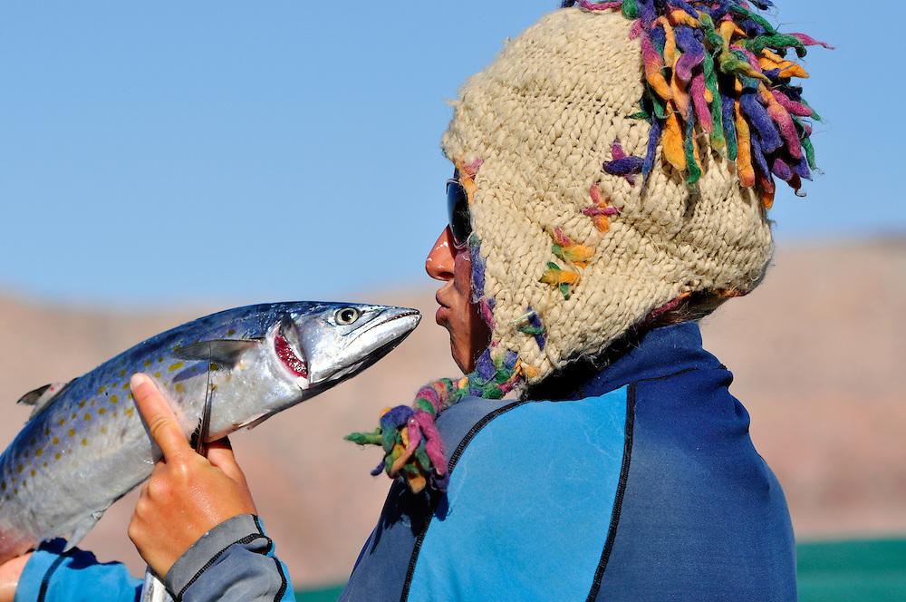 Woman pretending to kiss fish.