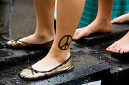 Peace sign on girls ankle, at the Anti-war march, 22nd July, 2006, London, UK
