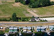Nederland, Gelderland, Maasbommel, 08-07-2010; recreatiegebied De Gouden Ham, onderdeel van rivier de Maas met drijvende woningen aan de Bovendijk. De recreatiewoningen maken onderdeel uit van een complex van buitendijks gebouwde tweede huizen, die (gaan) drijven bij hoog water. De woningen zijn bevestigd aan meerpalen om verschillen in waterhoogte op te vangen. De amfbische huizen gaan alleen drijven bij hoog water..The Golden Ham recreation site, part of the river Meuse with floating houses on the Bovendijk (Upper Dike). The holiday homes are part of a  complex of houses build outside the dike that will rise and fall with the water level. The houses are attached to bollards to compensate water level fluctuations. The amphibious houses will only float at high waters..luchtfoto (toeslag), aerial photo (additional fee required).foto/photo Siebe Swart